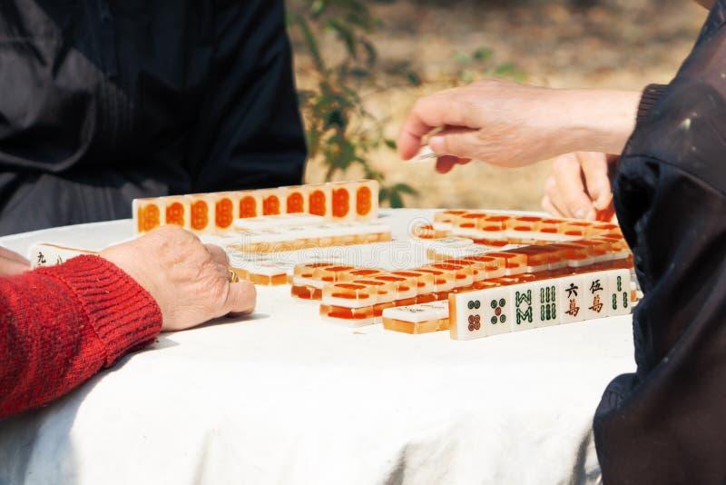 Mahjong-Tabellenglücksspiel des chinesischen Seniors auf Stadtstraße stockfotografie