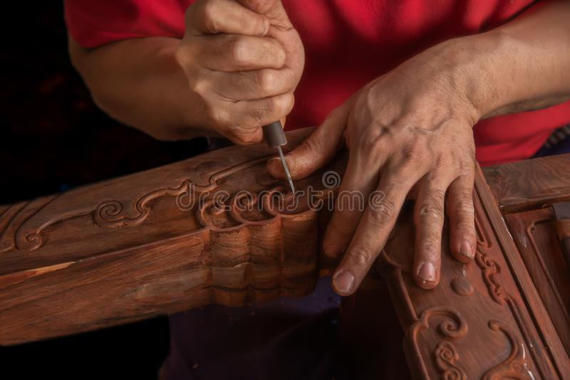 Carving and polishing of mahogany furniture. In the mahogany furniture factory, the workers work in the workshop royalty free stock photo