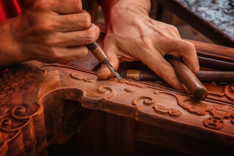 Carving and polishing of mahogany furniture. In the mahogany furniture factory, the workers work in the workshop royalty free stock photos