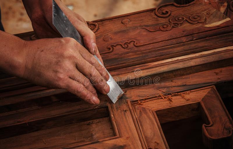 Carving and polishing of mahogany furniture. In the mahogany furniture factory, the workers work in the workshop stock image