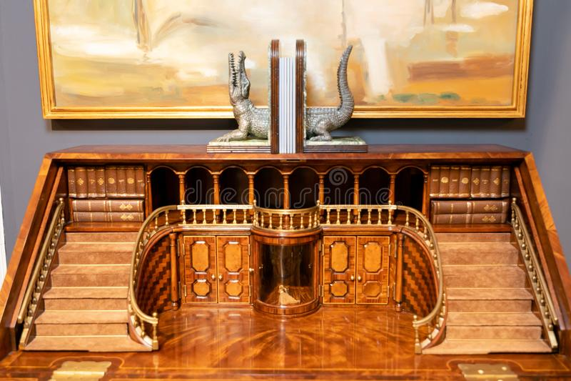 Mahognymöblemang med formgivaren hand-sned trä i formen av foajén och balkongen Mot en grå vägg och en bild arkivfoton
