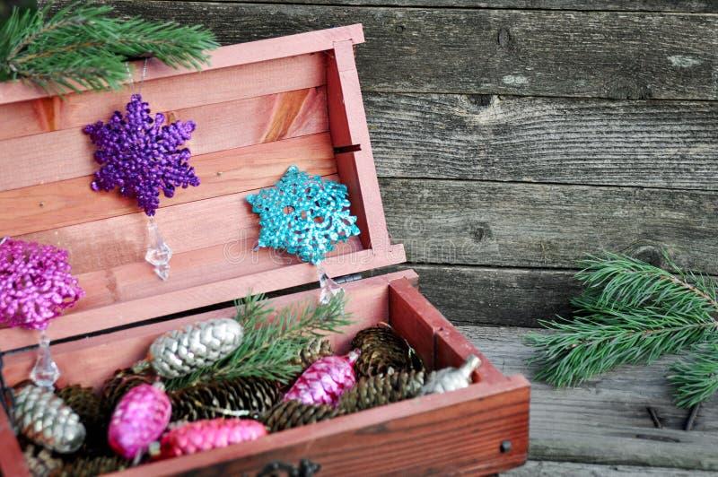 Mahoniowy drewniany pudełko z choinek dekoracjami, złoto konusuje i sosna rozgałęzia się na drewnianym szarym tle Zima wakacji co zdjęcie stock