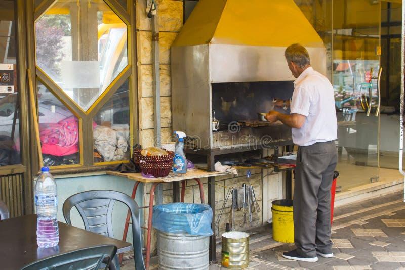 4 mai 2018 Un homme arabe de Druze faisant cuire la viande halal sur un barbecue de restaurant avec une cheminée d'extracteur d'a photos libres de droits