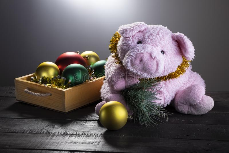 Maiale del giocattolo con il ramo dell'abete accanto alla scatola con le palle decorative di Natale su superficie di legno Chrism fotografia stock libera da diritti