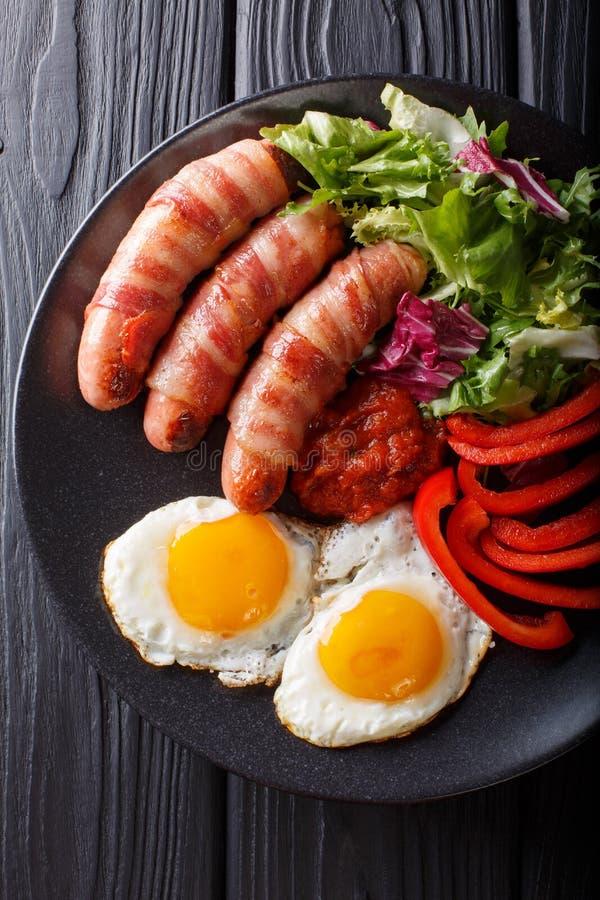 Maiali della prima colazione in salsiccie fritte coperte avvolte in bacon, uova fotografia stock