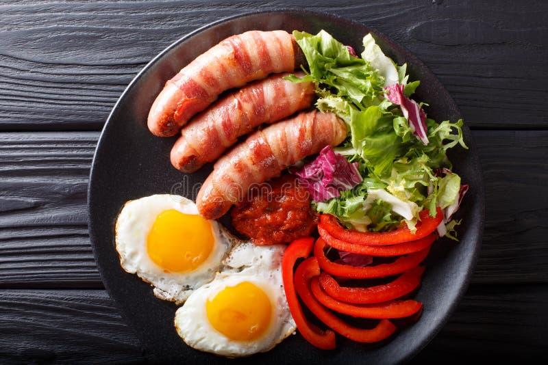 Maiali della prima colazione in salsiccie fritte coperte avvolte in bacon, uova immagini stock libere da diritti