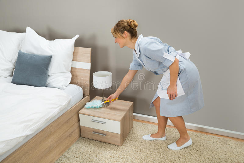 Maid cleaning dust with feather duster. Young Happy Maid Cleaning Dust With Feather Duster In Hotel Room stock photo