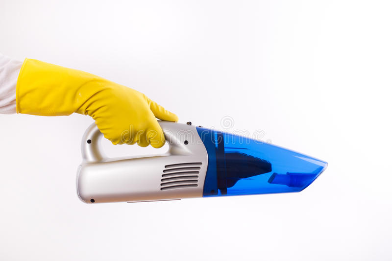 Maid holding vacuum cleaner on white. Close up of female hand with rubber gloves holding cordless vacuum cleaner isolated on white background royalty free stock photos