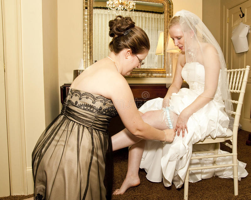 Maid of Honor Putting on Garter. The maid of honor putting the garter on the bride in the bride's dressing room stock photos