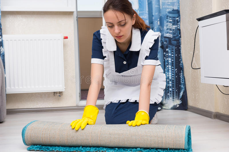 Maid or housekeeper doing the cleaning stock photography