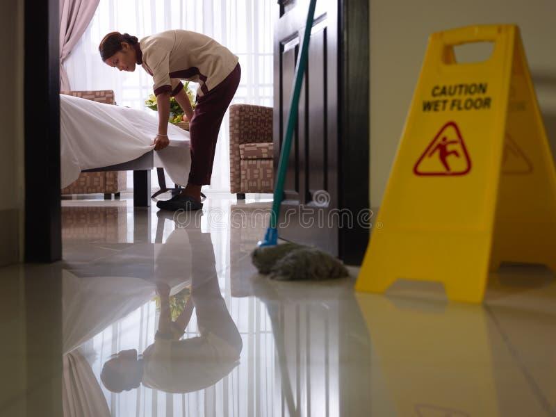 Maid på arbete och cleaning i lyxigt hotellrum royaltyfri bild