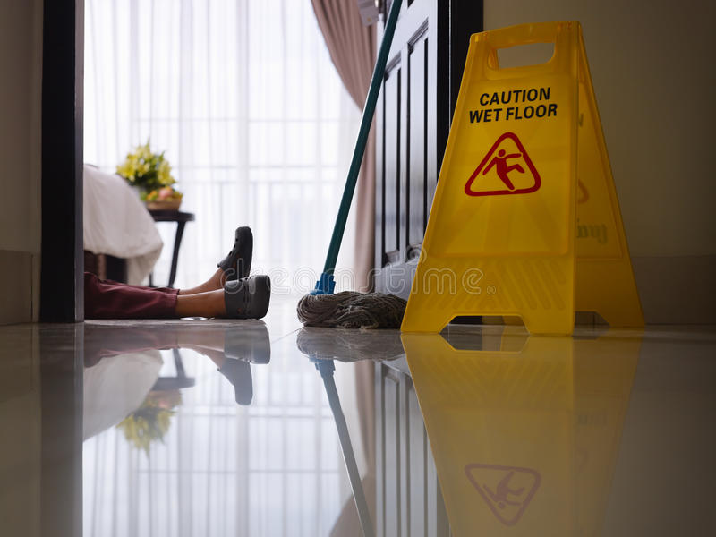 Maid slipped on wet floor and laying down stock photography