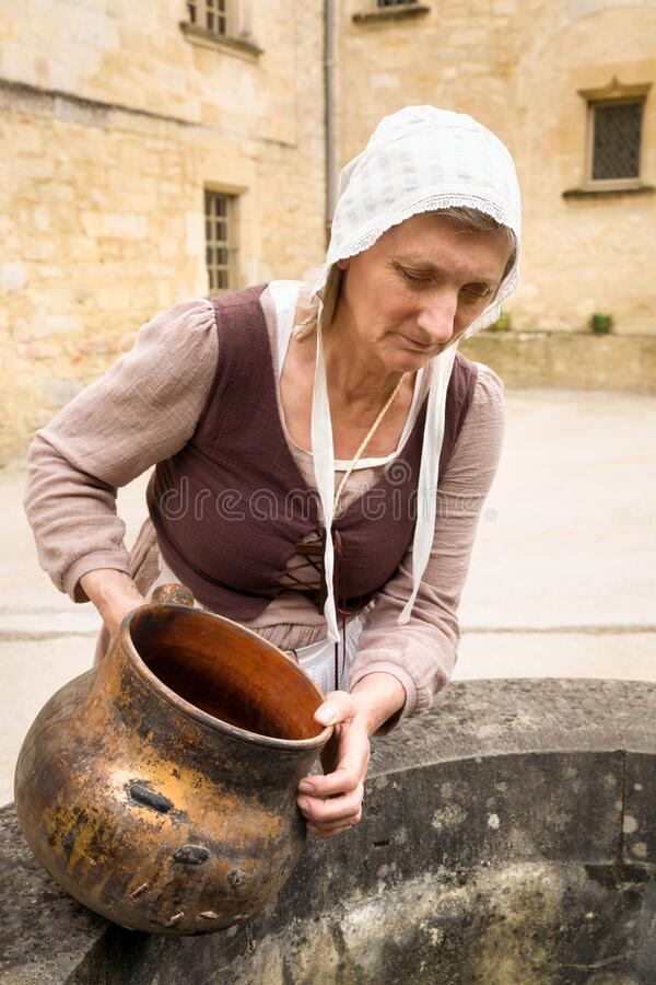 Maid working at water well royalty free stock photo