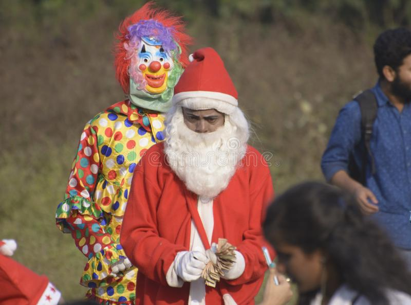 A boy dressed in Santa clause dress begs in the kolkata maidan on christmas stock photos