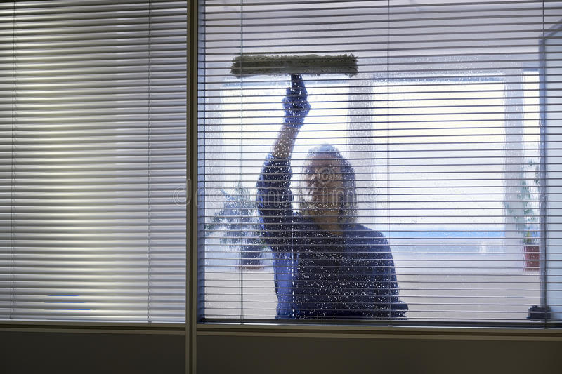 Maidcleaning och i regeringsställning avtorkingsfönster arkivbild