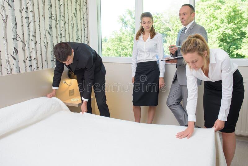 Maide que faz a cama no hotel fotografia de stock royalty free