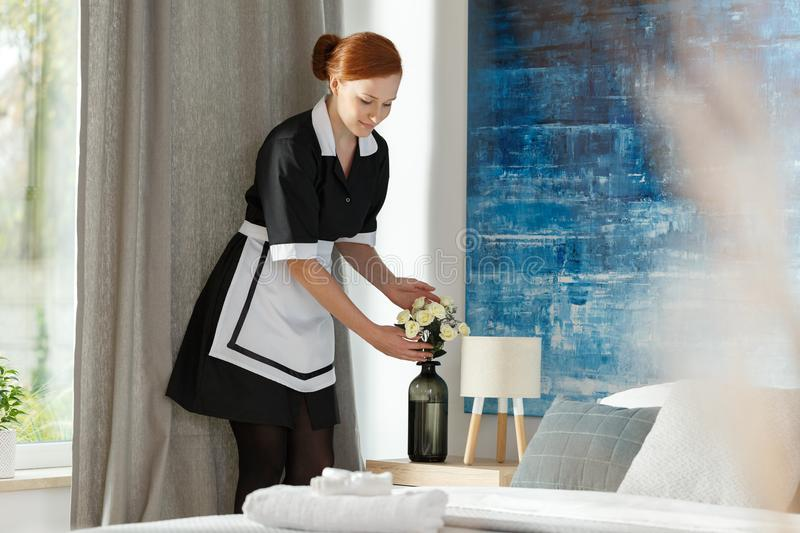 Maidservant putting flowers into vase royalty free stock photos