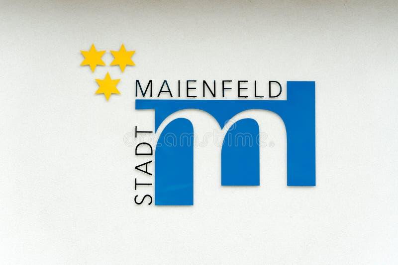 Maienfeld, GR/die Schweiz - 9. Juni 2019: Stadtsymbol und Flagge des Dorfs von Maienfeld mit deutscher Textlesung lizenzfreies stockbild