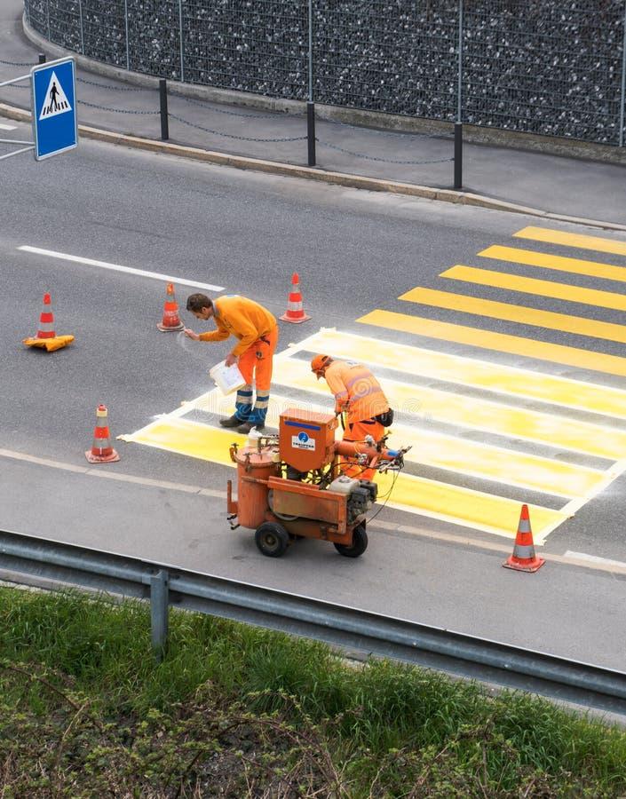 Maienfeld GR/Schweiz - April 2, 2019: arbetare som målar och markerar en fot- övergångsställe med ny gul målarfärg för att se til arkivfoto