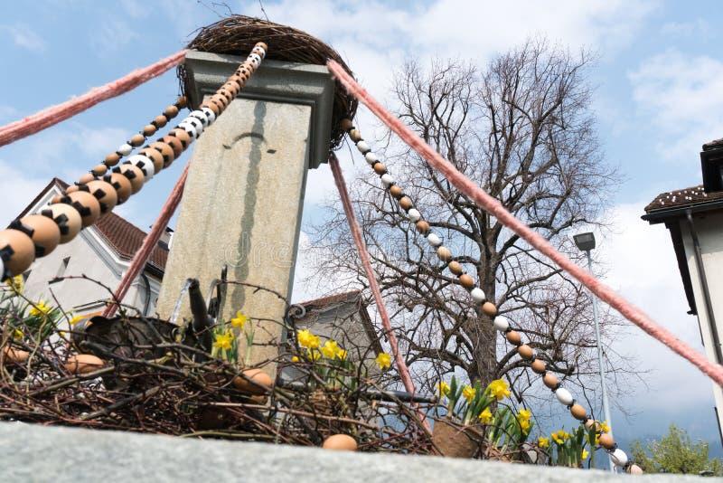 Maienfeld, gr./Zwitserland - April 1§3, 2019: feestelijke decoratie voor Pasen-vakantie op de dorpsfonteinen van de kleine sta stock fotografie