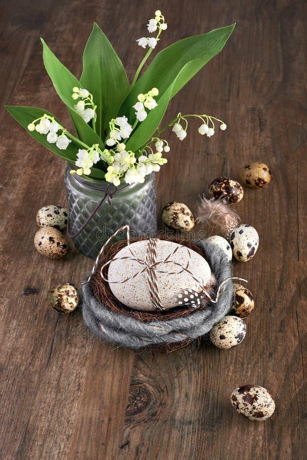 Maiglöckchen- und Ostern-Dekorationen auf altem Eichenholz stockfotografie
