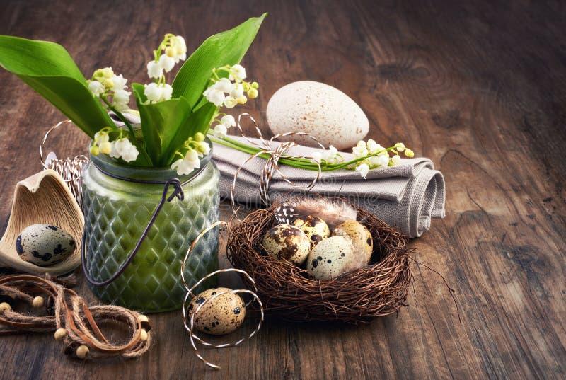 Maiglöckchen- und Ostern-Dekorationen auf altem Eichenholz stockfoto
