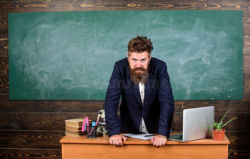 Maigre barbu sérieux strict d'homme de professeur sur le fond de tableau de table Sembler de professeur menaçant Directeur images libres de droits