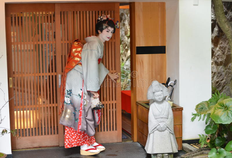 Maiko öffnet Schiebetür, Kyoto, Japan lizenzfreie stockfotografie