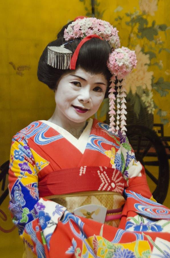 Maiko στο κόκκινο κιμονό με το χρυσό υπόβαθρο στοκ εικόνα