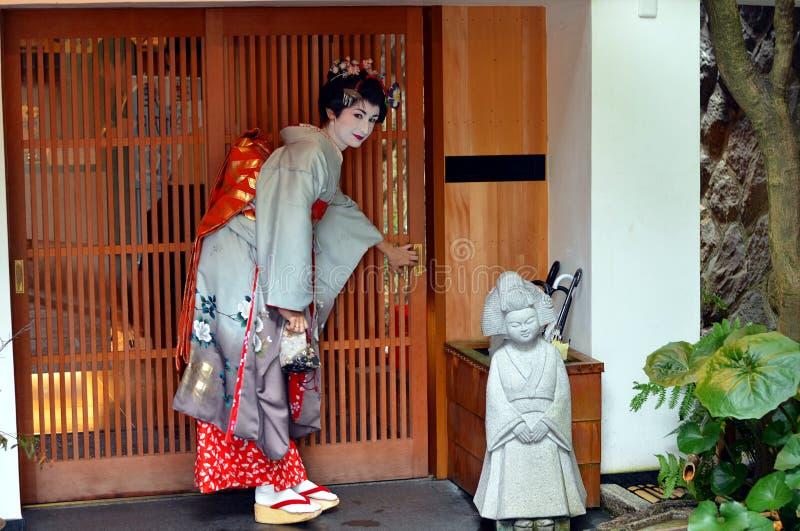 Maiko abre la puerta deslizante, Kyoto, Japón foto de archivo libre de regalías