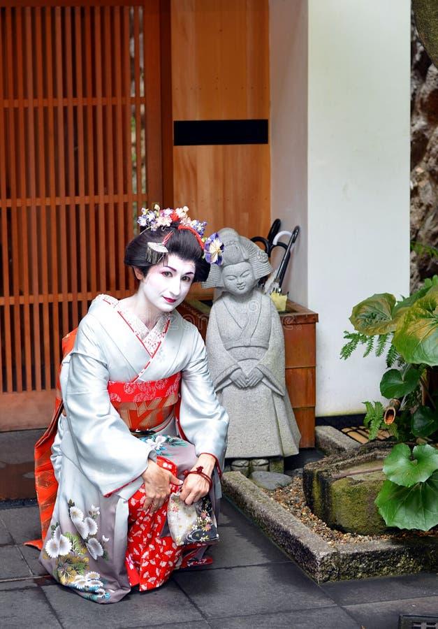 Maiko, das mit traditionellen japanischen Dekorationen, Kyoto, Japan aufwirft stockfotografie