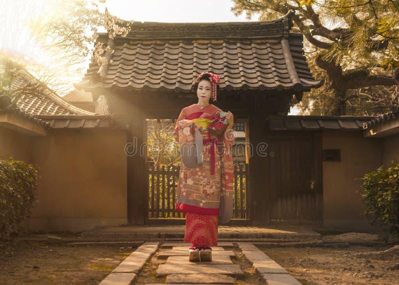 Maiko en un kimono que presenta en una trayectoria de piedra delante de la puerta de una casa japonesa tradicional rodeada por la foto de archivo libre de regalías