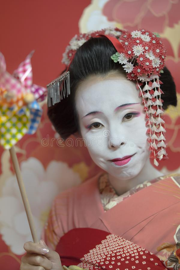 Maiko im Kimono, der eine bunte Rohrwindkraftanlage in der Hand hält stockfotografie