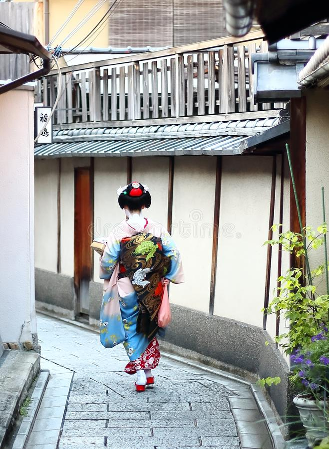 A maiko walking down the streets of Gion neighborhood in Kyoto. royalty free stock image