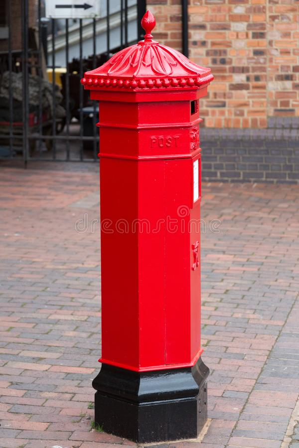Mail Box in Gloucester. Gloucester, United Kingdom - March 28, 2015: In traditional red a mail box sits on a street corner in Gloucester in England`s West royalty free stock images