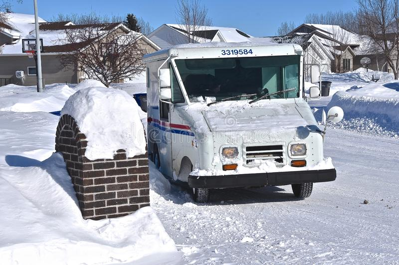 Mail carrier delivers mail for the USPS. MOORHEAD, MINNESOTA, February15, 2019: The mail carrier delivers daily mail in a snow covered neighborhood with a stock photos
