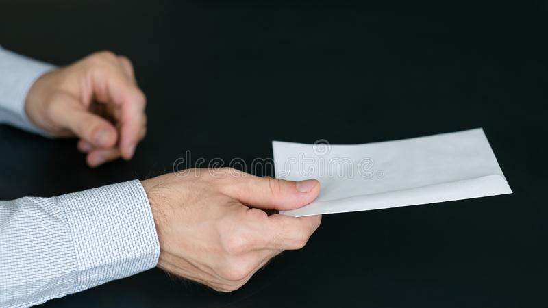 Mail delivery service man passing envelope letter. Mail delivery service. Cropped shot of man passing envelope with letter over dark background. Copy space royalty free stock photos
