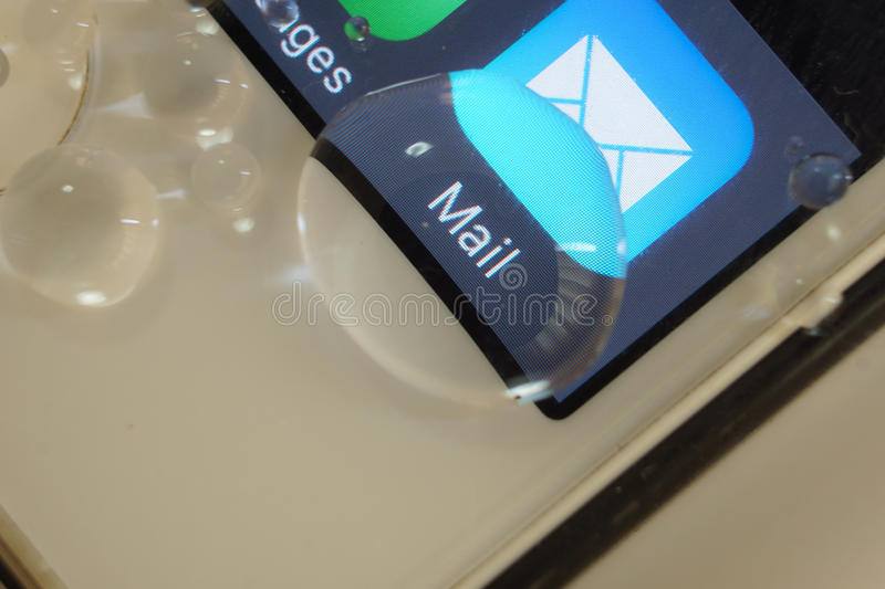 Mail magnified by drop of water. A word mail on telephone screen magnified with drop of water stock images