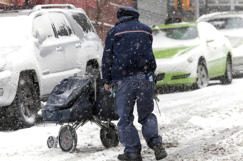 Mail man with carriage during snow storm. BRONX, NEW YORK -JANUARY 7: Mail man pushes mail carriage during snow storm. Taken January 7, 2017 in New York stock images