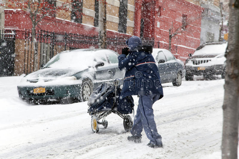 Mail man during snow storm in New York. BRONX, NEW YORK - JANUARY 21: A mail man works while weathering a 6 to 10 inch snow storm and teen temperatures along stock photos