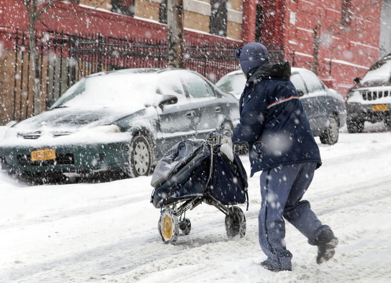 Mail man during snow storm in New York. BRONX, NEW YORK - JANUARY 21: A mail man works while weathering a 6 to 10 inch snow storm and teen temperatures along stock photography