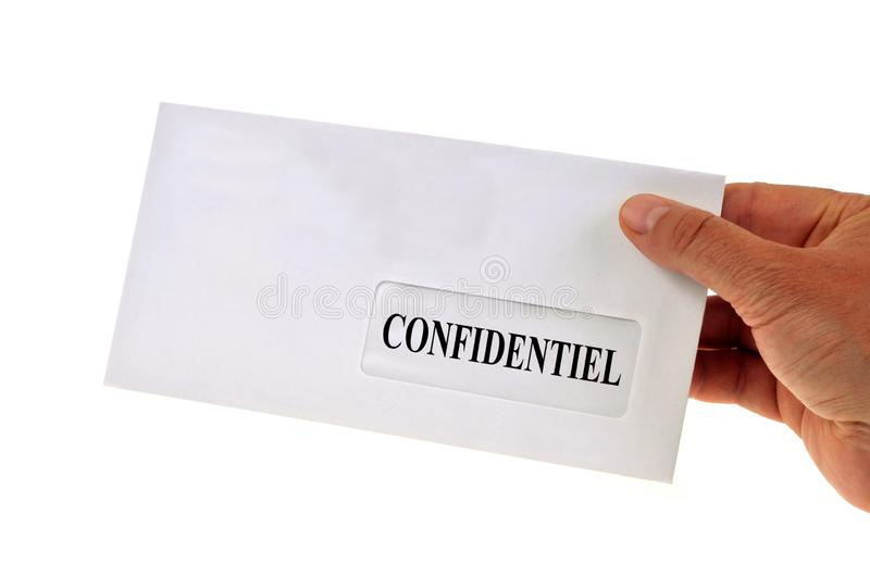 Confidential letter held in hand close up on white background. Mail must remain secret in a close-up envelope royalty free stock image