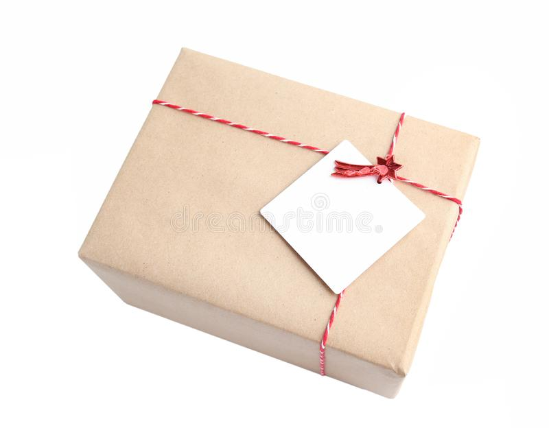 Mail parcel wrapped with craft brown paper with red twine isolated. royalty free stock photos