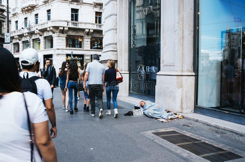 MAILAND, ITALIEN - 17. JUNI 2016: Leute, die durch schlafenden obdachlosen Mann mit hofame überschreiten (hungriger) Aufschrift i stockfoto