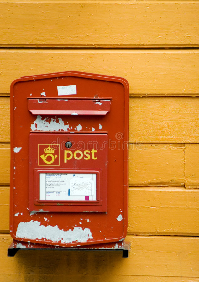 Mailbox in Norway. A red mailbox on a yellow, wooden wall of a house. Norway stock images