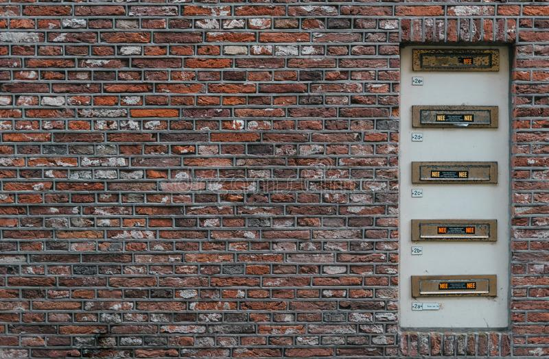 Mailbox slots on a industrial red brick wall background an old fashioned building. May be used in design and interiors royalty free stock images