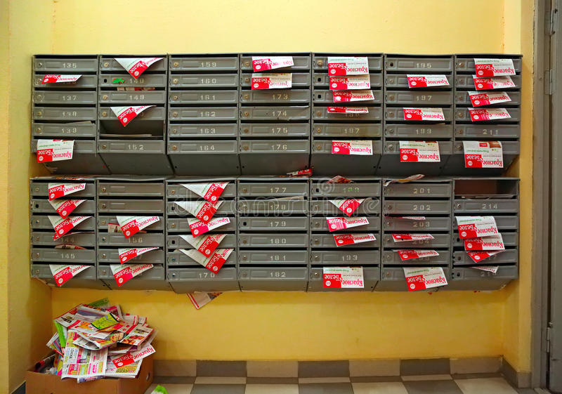 Mailboxes in the entrance hall of a residential house filled with paper flyers. Russia stock photography