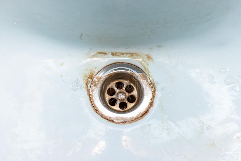 Maille sale de drain d'évier, trou avec le limescale ou l'échelle de chaux et rouille là-dessus, cuvette rouillée sale de salle d photographie stock
