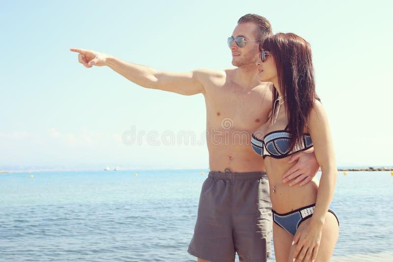 Maillot de bain de port de jeunes couples à la plage photo stock