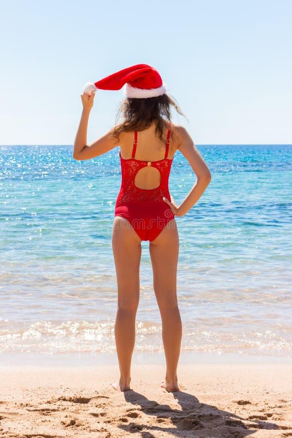 Maillot de bain de femme sexy et chapeau de port de Noël sur la plage Vacances d'hiver photo stock